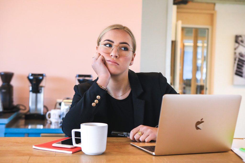 Eine Frau im Anzug sitzt an einem Tisch, vor Laptop und Kaffeetasse und denkt angestrengt-frustriert nach. Sie hat gerade erfahren, dass ihr ihr Nebenjob auf ALG 1 angerechnet wird.
