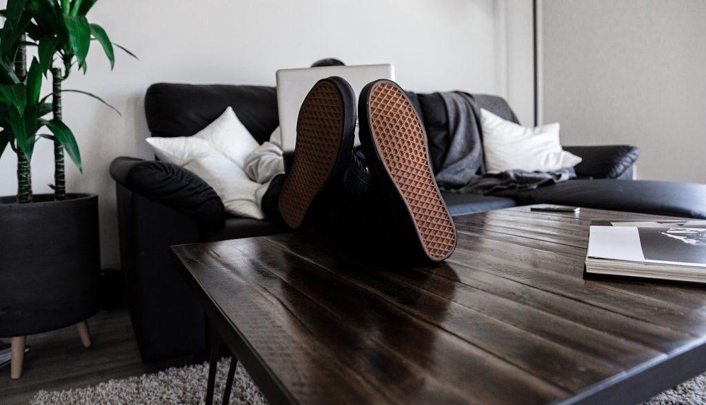 Ein Mann sitzt auf der Couch, die Füße auf dem Couchtisch. Er meldet sich gerade online arbeitslos.