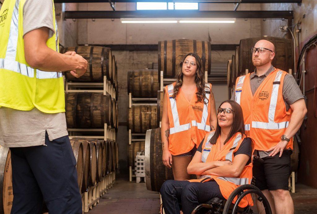 Drei Angestellte in orangen Warnwesten werden in einer Lagerhalle in eine Tätigkeit eingewiesen, eine davon sitzt im Rollstuhl.