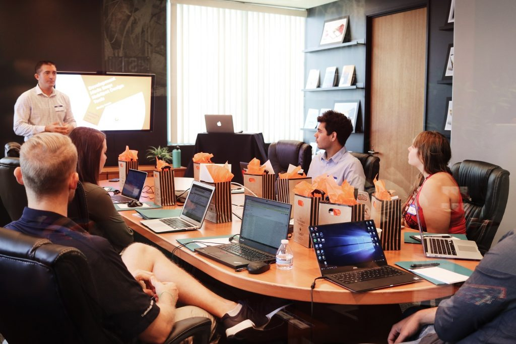 Ein Meeting mit mehreren Angestellten in einem Büro an einem länglichen Tisch. Ein Mitarbeiter steht vor dem Tisch und referiert.