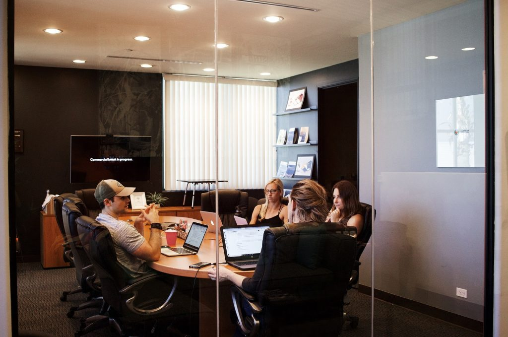 Ein Meetingraum mit einigen Mitarbeitern, die an einem halbvollen Tisch sitzen. Im Vordergrund ist eine durchsichtige Glastür.