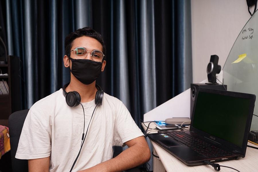 Ein junger Mann mit Kopfhörern um den Hals sitzt an einem Laptop in einem Büro. Er trägt eine Brille und einen Mund-Nase-Schutz und schaut in die Kamera. Er steht hier stellvertretend für Minijobber und Werkstudenten in der IT.