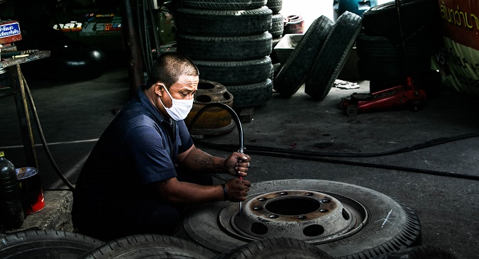 Ein KFZ-Mechaniker mit Mund-Nase-Schutz arbeitet an einem Reifen.  Er steht hier stellvertretend für Arbeiter und Angestellte in Kurzarbeit.