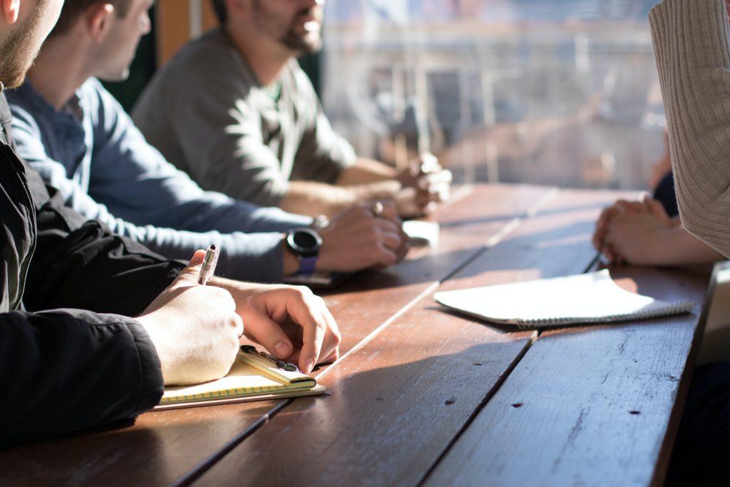Eine Gruppe von Menschen, scheinbar der Betriebsrat, sitzt an einem Holztisch.