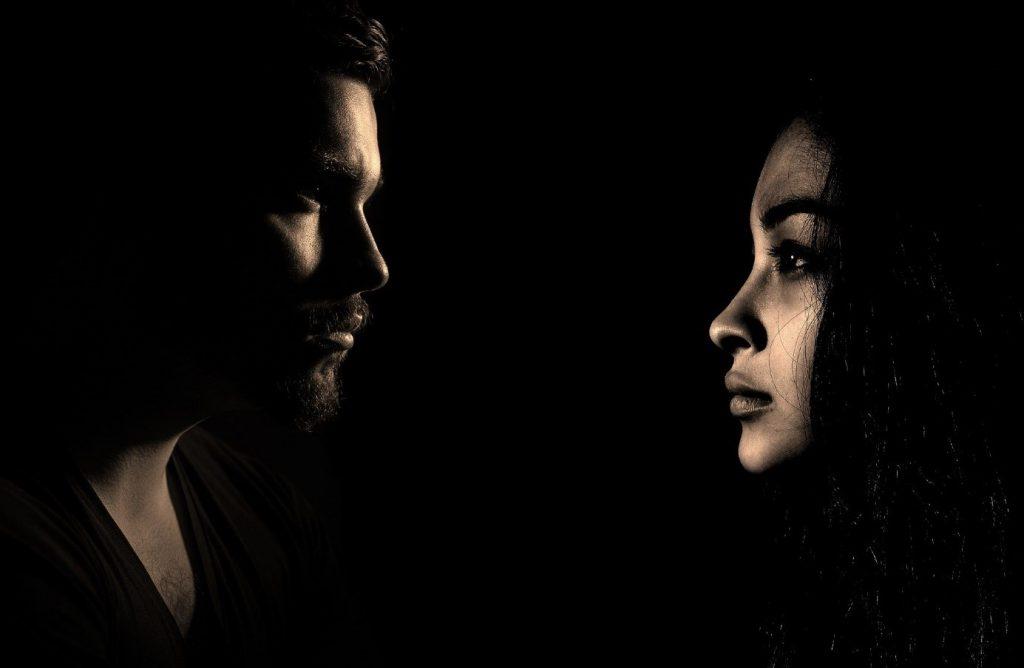 Ein Mann und eine Frau stehen im Dunkeln und starren aneinander vorbei. Sie wirken frustriert und erschöpft. Das Bild steht stellvertretend für den Frust und Streit, der im Zuge einer Trennungsunterhalts-Forderung zu Tage treten kann.