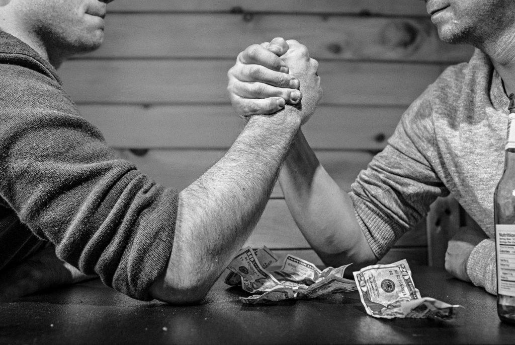 Zwei Männer sitzen am Tisch beim Armdrücken, neben ihnen liegen zerknüllte Geldscheine. Das Bild ist in schwarzweiß und symbolisiert das Hin und Her, dass bei einem Streit über den Trennungsunterhalt bis zur Scheidung entstehen kann.