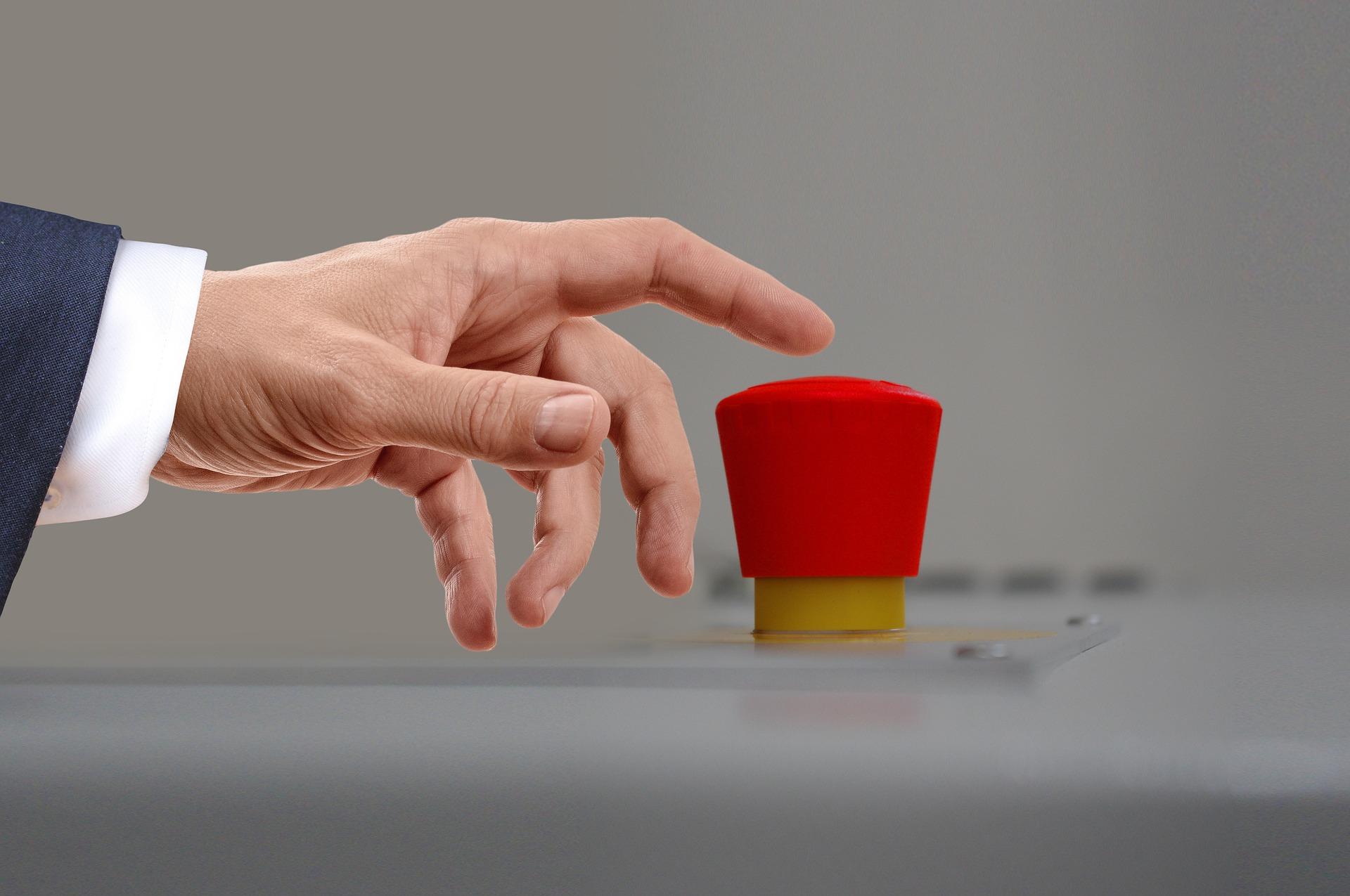 Abgebildet ist eine Hand eines Mannes, deren Zeigefinger über einem großen roten Knopf schwebt.