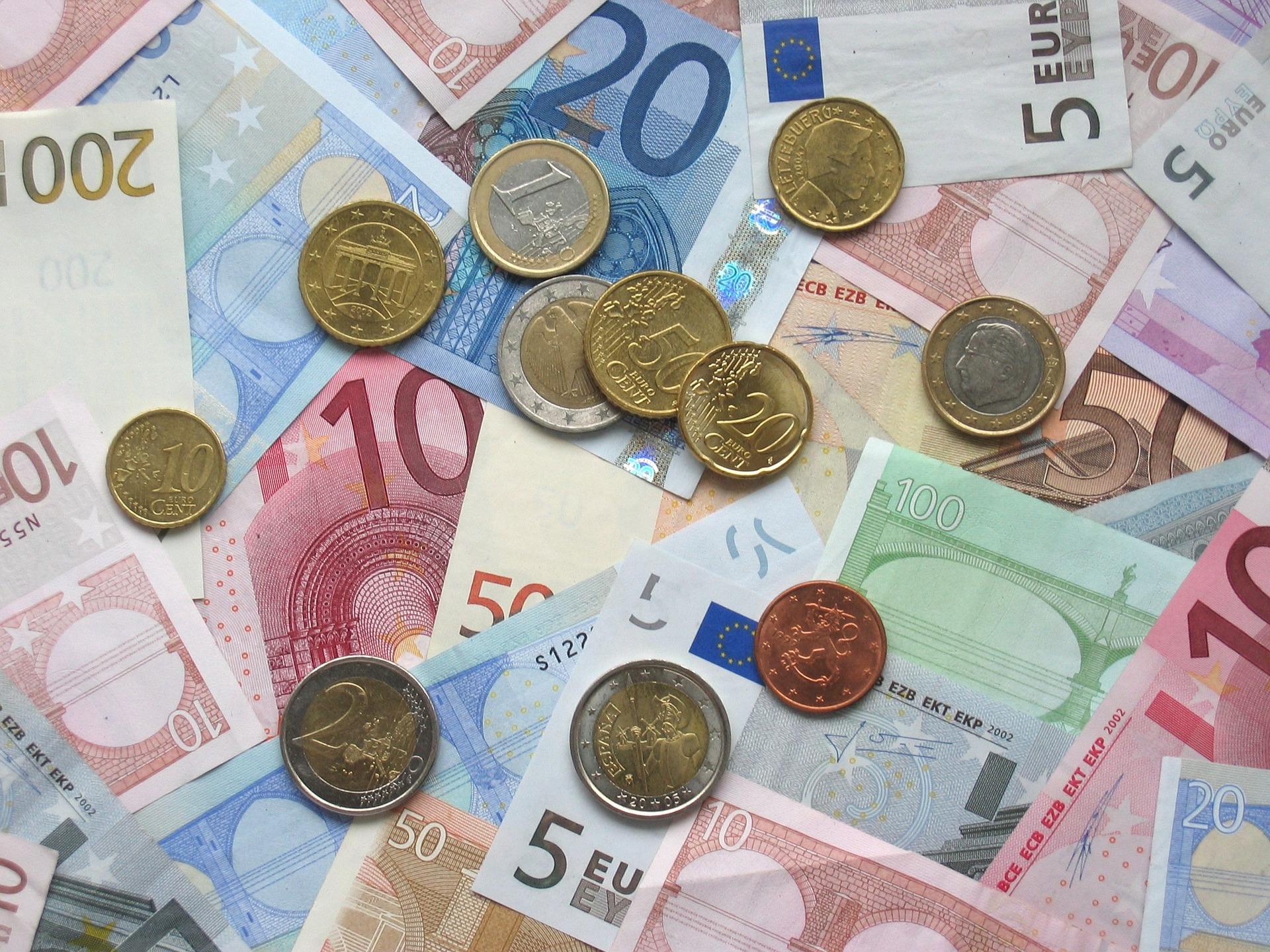 Verschiedene Euroscheine, die die gesamte Tischfläche abdecken. Zusätzlich wurden auf die Scheine einige Münzen drauf gelegt.