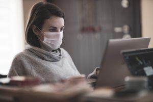 Frau mit Maske am Computer: Die Befreiung von der Maskenpflicht schützt nicht vor einer fristlosen Kündigung.