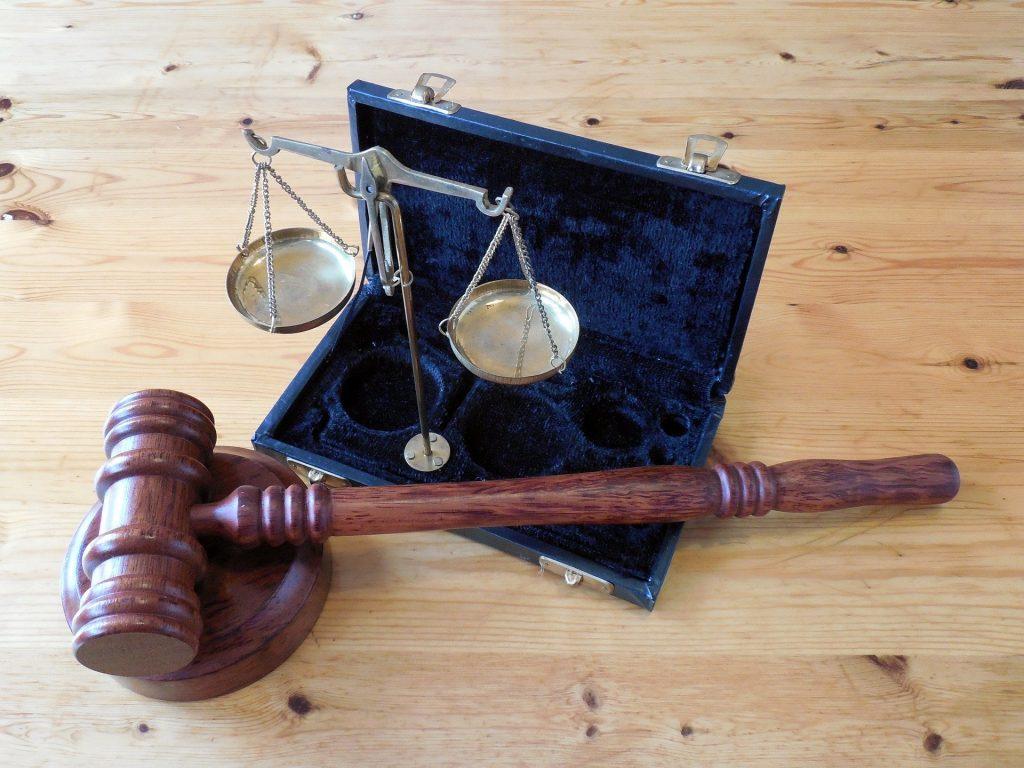 Ein Richterhammer mit Waage auf einem Holztisch. Das Bild symbolisiert einen Rechtsspruch in einer Kündigungsschutzklage.