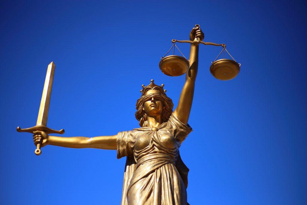 Auf dem Bild sieht man die Götting Justizia als Bronzestatue. Sie hält eine Waage und ein Schwert. Sie steht hier stellvertretend für den gangbaren Rechtsweg.