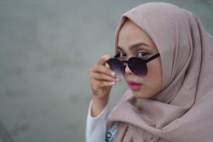 Frau mit Kopftuch und Sonnenbrille: Arbeitgeber dürfen das Tragen religiöser Symbole am Arbeitsplatz nur mit einer guten Begründung verbieten.