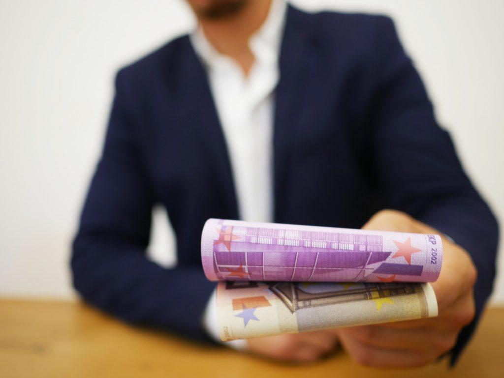 Ein Mann im Anzug übergibt Geldscheine in die Kamera. Man sieht nur seinen Torso, er selbst ist verschwommen, die Geldscheine scharf. Das Bild steht stellvertretend für die Bezahlung des Mitarbeiters.