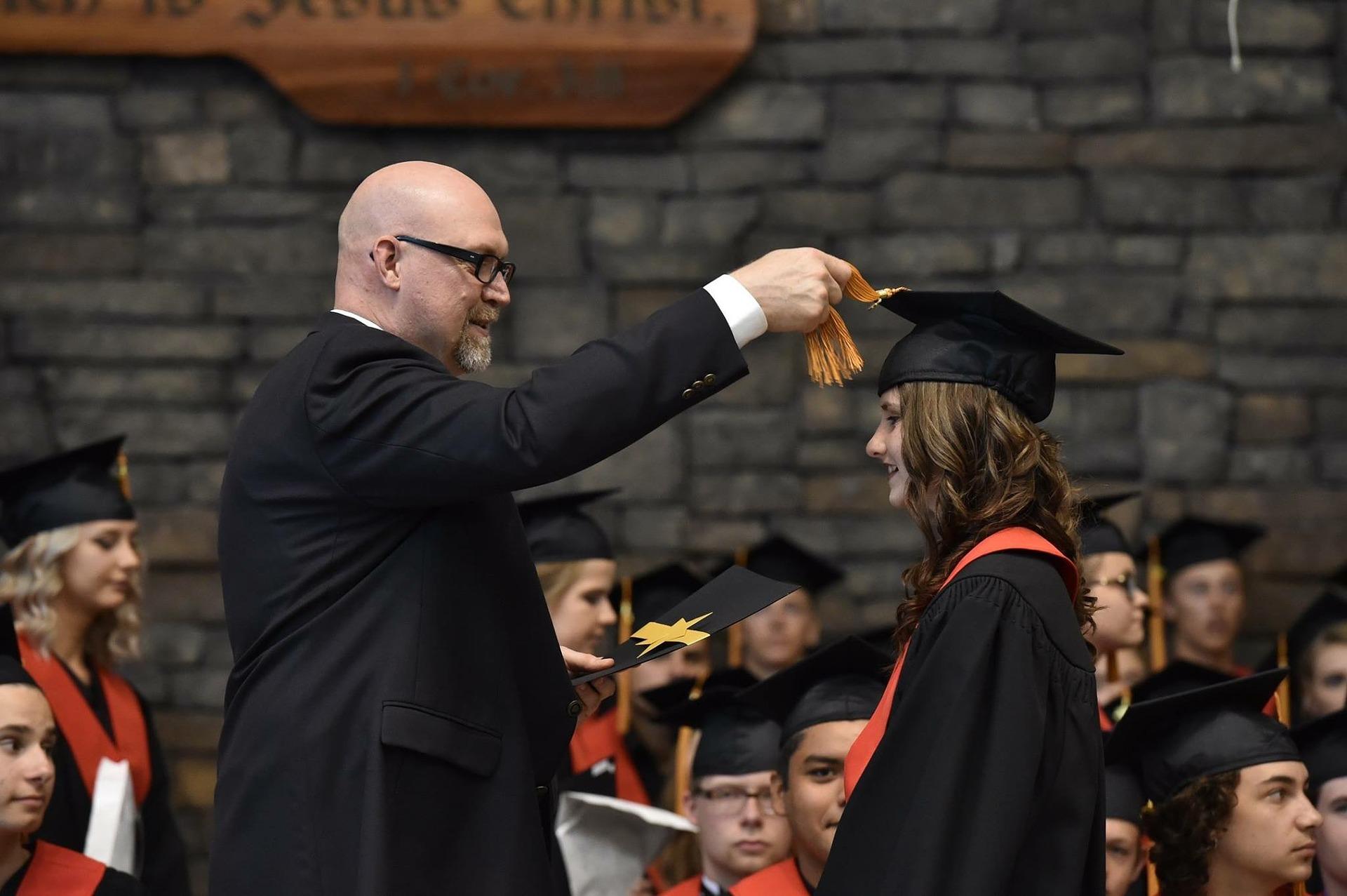 Eine Abschlusszeremonie, bei der ein Dozent der Studentin ihr Abschlusszeugnis überreicht.