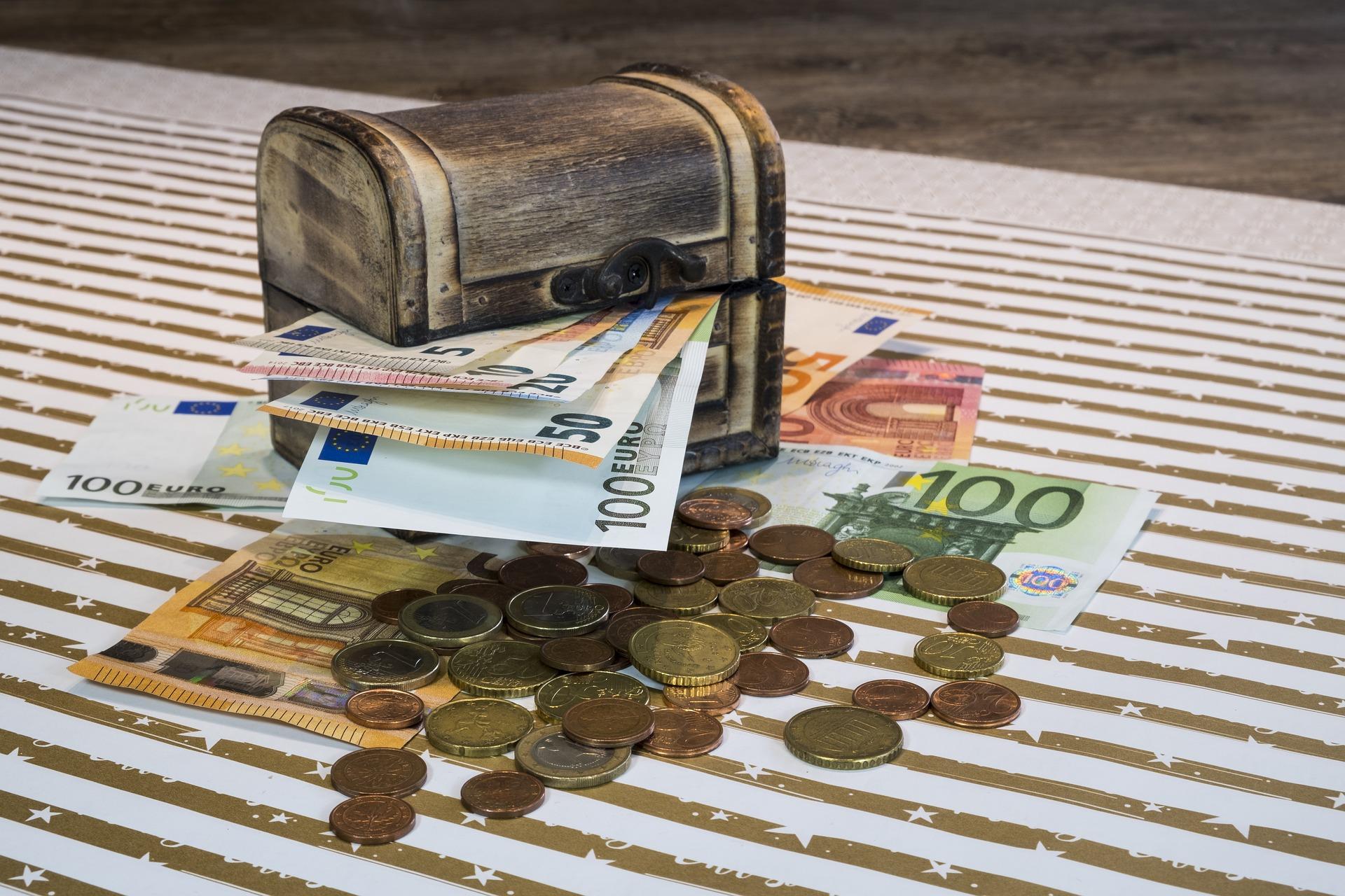 Eine kleine Schatztruhe, aus der mehrere Euroscheine mit verschiedenem Wert herausschauen, und mehrere Eurostücke wie auch -scheine, die um sie herum liegen.