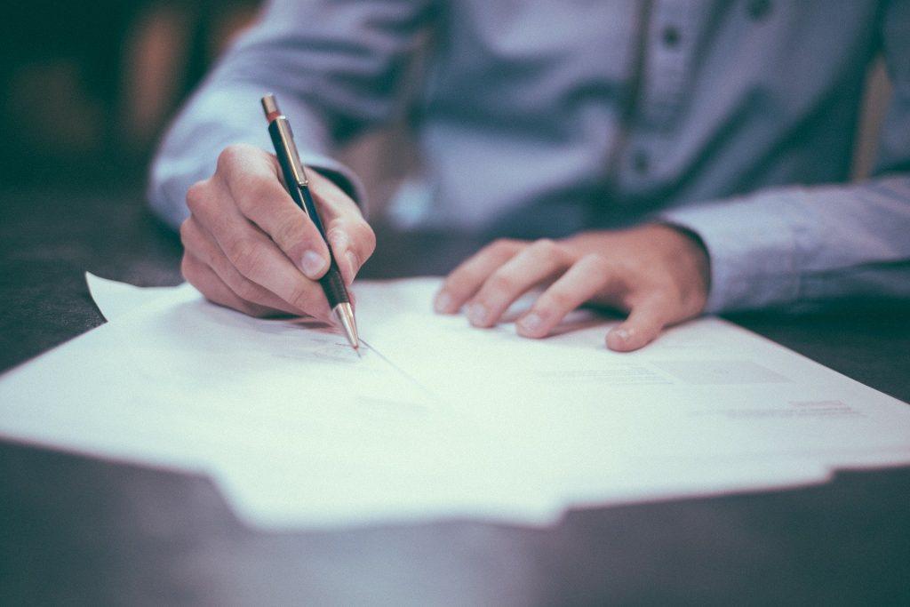 Man sieht Papiere auf einem dunklen Schreibtisch, ein Mann unterzeichnet sie. Das Bild steht für einen unterschriebenen Aufhebungsvertrag.