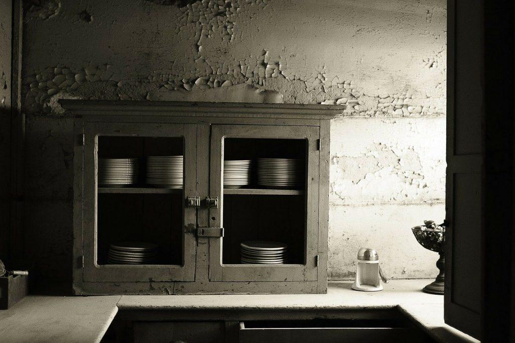 Ein alter Küchenschrank vor unverputzter Wand. Das Bild steht stellvertretend für die unsanierten Altbauwohnungen in Berlin, die der Mietendeckel oft in vollem Umfang betrifft.