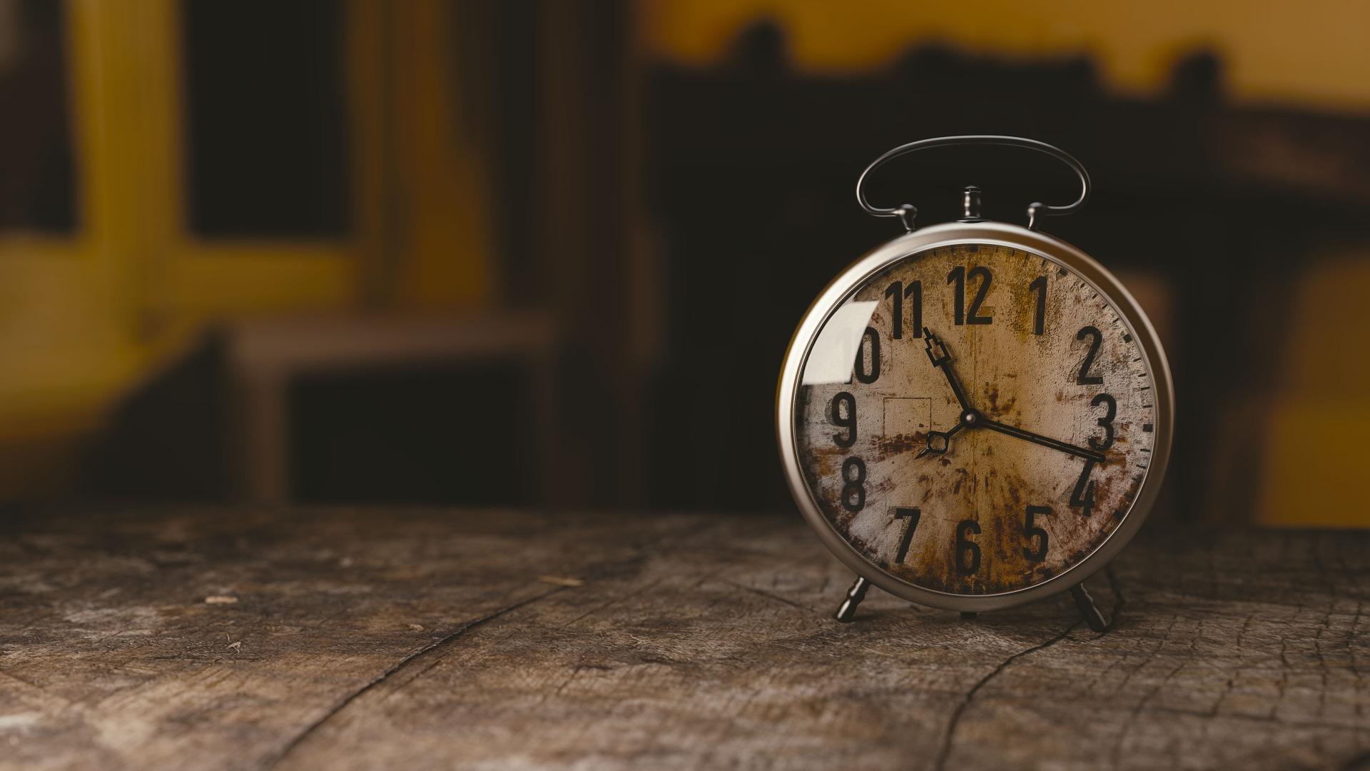 Eine alte Uhr, die auf einem Holztisch steht. Sie kann die Zeit zur Bezahlung von Erschließungskosten zeigen.